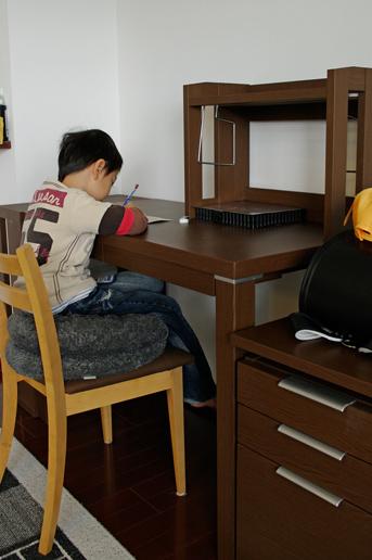 新しい学習机で宿題する兄