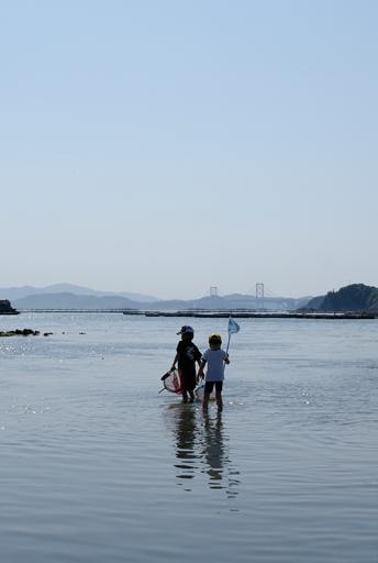 遠浅の海岸を楽しむ少年たち